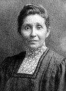 A Native American female wearing a dark shirt with a high collared white patterned chemisette. She has dark upswept hair, a solemn expression, and is facing the camera.