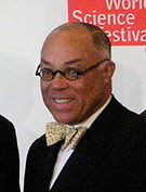 An African American male with graying hair and round eye glasses, wearing a suit with a bow tie, set against a white and red background reading World Science Festival.