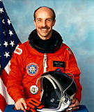 A Caucasian male astronaut in front of the American flag wearing an orange jumpsuit while holding a helmet.
