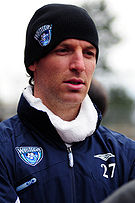 A Caucasian male wearing a blue winter jacket and a black cap both with a sports logo, a soccer ball with a wave superimposed, for the soccer team the Vancouver Whitecaps. The jacket also sports the number 27 and the subject is staring off camera.