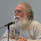 A Caucasian male with gray hair and a white beard and mustache sitting in front of a microphone while wearing a white long sleeved shirt and glasses.