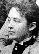 A Caucasian female in profile wearing a high collared shirt with upswept hair.