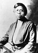 An African American female with short dark hair, round eye glasses, and a solemn expression sitting down and facing the camera.