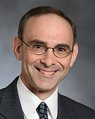 A Caucasian male with brown hair and eye glasses, wearing a suit and tie, smiling at the camera.