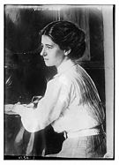 A Caucasian female sitting at a desk holding a pen, with her face in profile. She is wearing a white high collared long sleeved shirt, belt, and checkered bottom with dark upswept hair.
