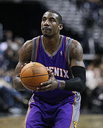 "A man, wearing a purple jersey with a word ""PHOENIX"" written in the front, is holding a basketball."