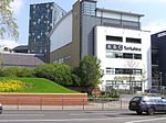 """A quirky modern five-storey building with a large sign saying """"BBC Yorkshire"""" in black above the second-floor windows on the white-fronted facade of the lower four floors can be seen on the far side of a dual-carriageway road with a barrier along the central reservation. At right-angles to the right of the building is a tall blue slab with the letters """"BBC"""" in white at the top. The left side of the building is mostly brick-red with a few windows, but above it is a light blue windowless section. The roof above this and the grey fifth floor of the frontage curves gently down to the rear. A lone car is driving from left to right along the road;  between it and the building, temporary boards have been erected in front of a building to the left. In the top left-hand corner of the picture, part of a tall many-windowed building can be seen."""