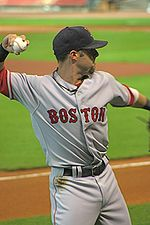 """A man in a gray baseball uniform with """"BOSTON"""" across the chest and a dark cap prepares to throw with his right arm."""