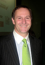 A smiling man wearing a white shirt with a green tie and black jacket