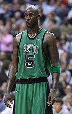 "A man, wearing a green jersey with a word ""BOSTON"" and the number ""5"" written in the front, is standing in front of the crowd."