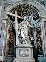 A marble statue showing a matronly woman in a sweeping cloak supporting a cross which stands beside her and gesturing to the viewer with her left hand