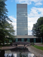 Blue/Grey skyscraper with a glass curtain wall. In the foreground is park pond with a small wooden bridge and trees at either side. In between the Tower and the pond is a modern 2 storey building