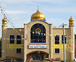 """A large symmetrical two-storey building of yellow brick. The centre bay, incorporating the entrance, juts out. It has a large window with a semicircular top on the first floor and above is a golden onion dome on a blue base. At the ends of the frontage are hexagonal pilasters with small octagonal windowed pavilions and onion domes on top. Above the entrance is a white sign saying """"The Sikh Temple"""" in blue. Each side has one two-storey and one one-storey window, and also yellow banners alongside the Temple's name. On each side of the entrance is a wooden seat, and strings of bunting are stretched across the scene."""