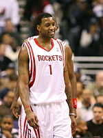 "A man, wearing a white jersey with a word ""ROCKETS"" and the number ""1"" written in the front, is walking on a basketball court."