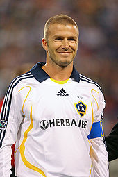 A photograph of a smiling man with a shaven head. He is wearing a white shirt with yellow trim and a navy blue collar, and a light blue armband.