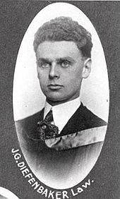 "Formal photo portrait of Diefenbaker at age 23. His short dark hair is very thick and curly and has been combed back smoothly, and his face is thinner than at an older age. He is formally dressed with a stiffened shirt collar and wears an academic hood. Picture is inscribed ""J.G. Diefenbaker, law""."