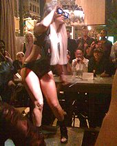 Full right profile of a young blond woman, surrounded by sitting spectators in a pub. She wears a black leotard and her long hair falls around her side. With her right hand she holds a pair of video sunglasses to her eyes.