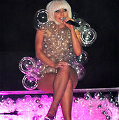 A blond woman in a bob-cut, sitting cross-legged on a transparent platform full of bubbles and lit from inside in pink. The woman is wearing a dress made of transparent bubbles of varying sizes. She is holding a microphone in her left hand and appears to be smiling.