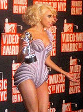 Right profile of a young blond woman. She wears a mauve leotard with purple stripes. Her hair is curled up behind her head. She holds a silver trophy in her right hand. A black background with red letters is visible behind her.