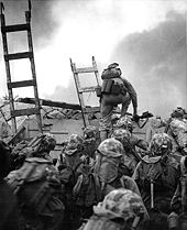 black & white photo of Marines using ladders to scale a seawall
