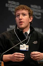 """Waist high portrait of man in his thirties, looking into the camera and gesturing with both hands, wearing a black pullover shirt that says """"The North Face"""" and wearing identification on a white band hanging from his neck"""