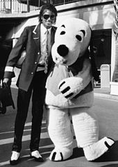 A black and white image shows a man standing next to a person dressed in a full dog costume. The man on the left has his left arm around the waist of the other person and is smiling.
