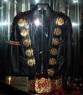 A black jacket with five round golden medals on its left and right shoulders and a gold band on its left arm sleeve. The jacket has two belt straps on the right bottom sleeve. Underneath the jacket is a golden belt, with a round ornament in its center. There is a red light reflecting on the jacket and belt as well as a gold colored plate on the left side of the jacket and belt.