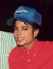 In the center for the photo, a light skinned male with black hair wearing a red shirt and blue cap can be seen. The male is smiling while titling his head to his right. Behind him, there is a black background and the shoulder of another person.
