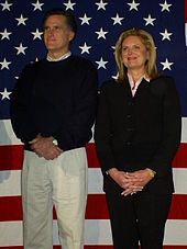 Mitt and Ann Romney standing side by side against an American flag