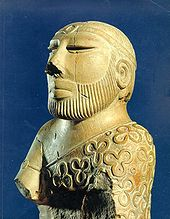 A carved stone statue of a bearded man with a prominent nose wearing a garment with a pattern
