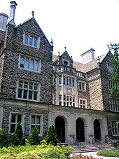 A four-story Gothic building with three entrance archways and historic balconies with evergreen trees at base and stairwells leading to each entrance