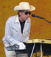 Dylan, wearing a white shirt and pants, sunglasses and a cowboy hat, plays the keyboards onstage.