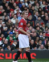 A side-on photograph of a man with red hair. He is wearing a red shirt, white shorts and black socks.