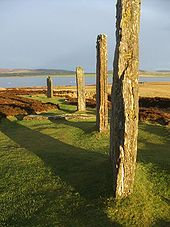 Four large standing stones sit in a field of grass and heather. They are illuminated by reddish sunlight and they cast long shadows to the left. A lake and low hills lie beyond.