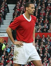 A photograph of a man with very short, dark hair. He is standing with his hands on his hips, and he is wearing a plain red shirt with a white collar and white shorts.