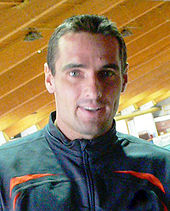 Roman Sebrie headshot with him wearing a black tracksuit top with red trim