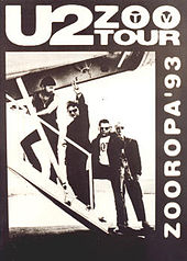 """A black poster with a black-and-white image occupying most it. The image shows U2 walking up the stairs of a small airplane as Bono gives a peace sign towards the viewer. Text on the poster reads """"U2 Zoo TV Tour"""" and """"Zooropa '93""""."""