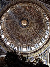 Photo looking up at the dome's interior from below. The dome is decorated at the top with a band of script. Around its base are windows through which the light streams. The decoration is divided by many vertical ribs which are ornamented with golden stars.