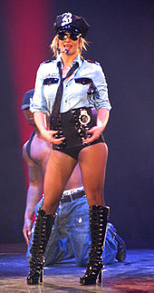"A female blond performer. She wears a policewoman light blue shirt, high-waisted black shorts with handcuffs attached to them, laced-up boots, a black police hat with a sparkly ""B"" in the middle, a black tie and aviator sunglasses. She holds a black baton between her right hip and her right arm. An African American man behind her is kneeling behind her, shirtless and wearing ."