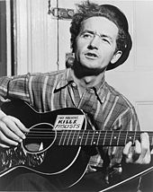 """Half-length photo of a middle-aged man sitting in front of a closed door and playing a guitar and singing. His wavy black hair is partly covered  by a black hat tipped at a rakish angle. He wears a striped flannel work shirt. His black guitar has a sign on it that says, """"This machine kills fascists""""."""