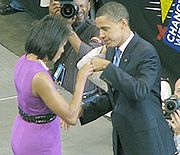 """The Obamas face each other and bump fists on stage. She wears a purple dress and he wears a dark suit. Several signs read """"CHANGE WE CAN BELIEVE IN"""" and several photographers take photos."""