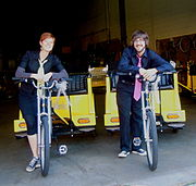 Young woman at left and young man at right, both wearing navy blue, standing on two yellow pedicabs.