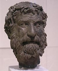Bronze head of bearded man with furrowed brow and unruly hair