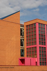 An orange brick building with pink window frames and a blue roof