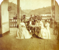 a man and three women seated around a table with two servants standing in the background
