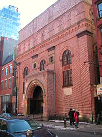 A five-story square building directly abuts a sidewalk. The facade is reddish brick, with two square windows on the second and three arched windows on the third floor. The main entrance juts forward from the facade, and is topped by an arch.