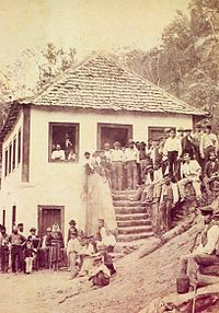 Photograph showing a crowd of people gathered around and on the steps of a white stuccoed house with a hip roof covered in wood shingles situated on a steep slope of a forested hill