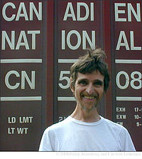 """Head and shoulders photograph of a bearded smiling man in white T-shirt standing in front of a freight car bearing the words """"Canadien National"""" and loading information"""