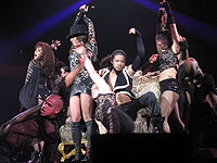 Britney Spears surrounded by a group of dancers. They are all wearing black outfits made of lace and leather.