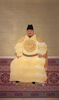 A middle aged bearded man wears yellow robes with dragons inscribed and a black hat, and sits on a throne.